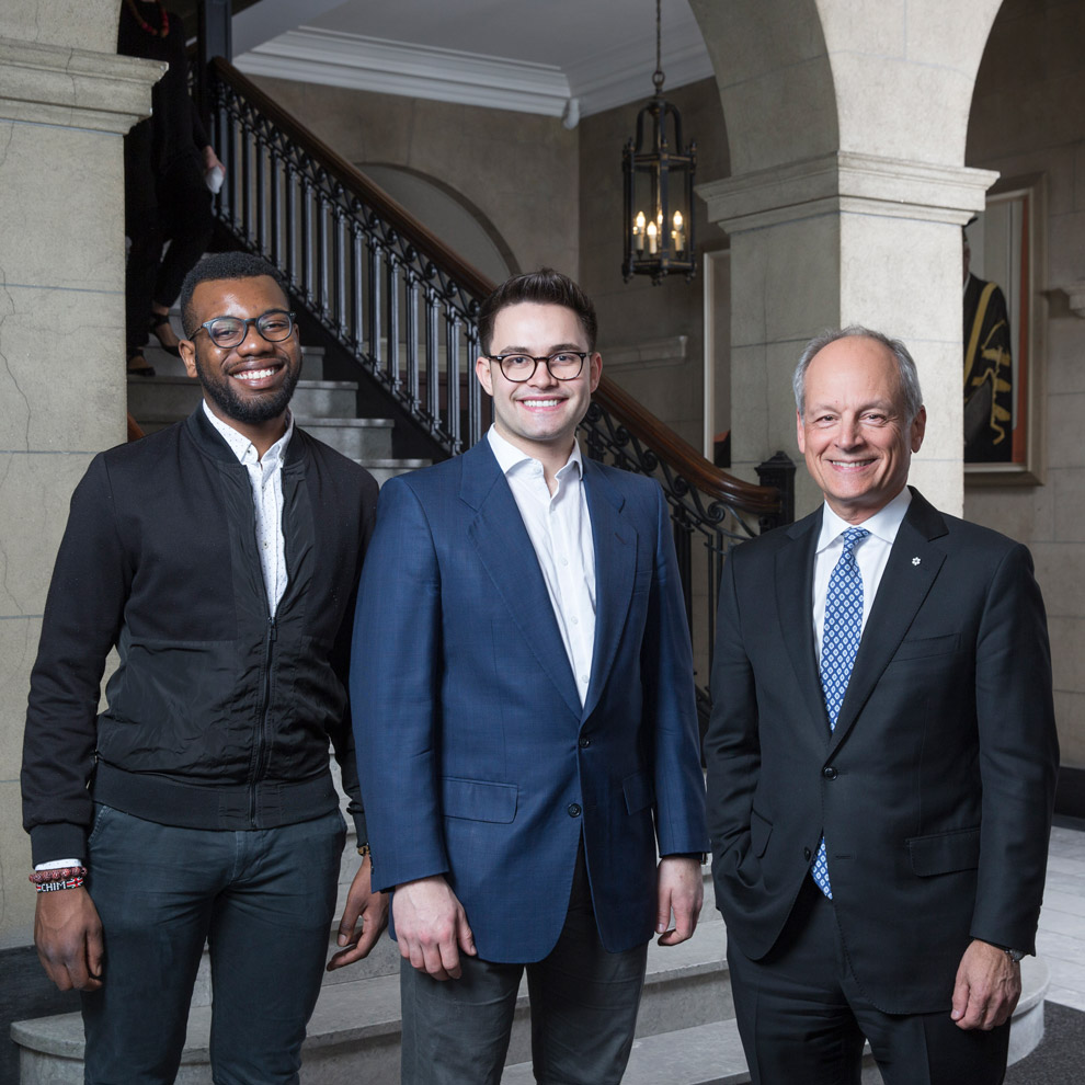 Chim Alao, Mathias Memmel and Meric Gertler smile and stand in a row in front of a staircase, indoors