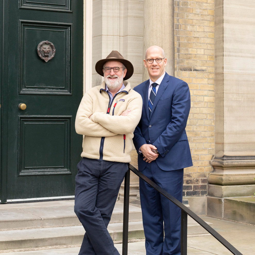 Scott Mabury and Donald Ainslie stand together, smiling, in front of the door to Simcoe Hall